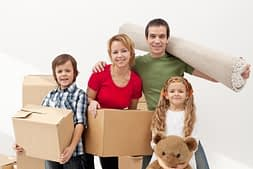 family carrying household items in boxes