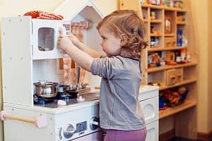 Child playing with toy kitchen